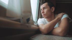 Λυπημένος ατόμων που τρυπιέται παράθυρο οδηγώντας έναν σιδηρόδρομο τραίνων φαίνεται έξω το ταξίδι ταξιδιών σιδηροδρόμου τραίνων τ απόθεμα βίντεο