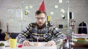 Λυπημένος ελκυστικός αποτελεσματικός επιχειρηματίας που γιορτάζει μόνα γενέθλια στο γραφείο, φυσά ένα κερί σε ένα μικρό κέικ απόθεμα βίντεο