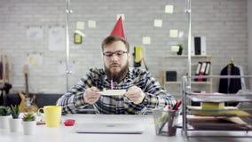 Λυπημένος ελκυστικός επιχειρηματίας που γιορτάζει μόνα γενέθλια στο γραφείο, φυσά ένα κερί σε ένα μικρό κέικ Είναι απόθεμα βίντεο