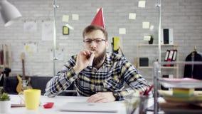 Λυπημένος ελκυστικός προσηλωμένος επιχειρηματίας που γιορτάζει μόνα γενέθλια στο γραφείο, φυσά ένα κερί σε ένα μικρό κέικ απόθεμα βίντεο