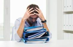 Λυπημένος επιχειρηματίας με το σωρό των φακέλλων στο γραφείο Στοκ εικόνες με δικαίωμα ελεύθερης χρήσης