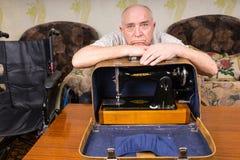 Λυπημένος ηληκιωμένος που κλίνει σε μια ράβοντας μηχανή σε μια περίπτωση Στοκ Εικόνες