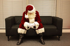 Λυπημένος και καταθλιπτικός Άγιος Βασίλης που περιμένει την εργασία Χριστουγέννων Στοκ Φωτογραφίες