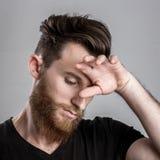 Λυπημένος και δυστυχισμένος νεαρός άνδρας που απομονώνεται στο γκρίζο backround Στοκ εικόνα με δικαίωμα ελεύθερης χρήσης