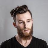 Λυπημένος και δυστυχισμένος νεαρός άνδρας που απομονώνεται στο γκρίζο backround Στοκ Φωτογραφίες