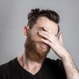 Λυπημένος και δυστυχισμένος νεαρός άνδρας που απομονώνεται στο γκρίζο backround Στοκ φωτογραφίες με δικαίωμα ελεύθερης χρήσης