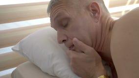 Λυπημένος, καταθλιπτικός κουρασμένος νεαρός άνδρας στο κρεβάτι απόθεμα βίντεο