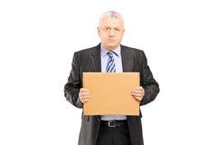 Λυπημένος μέσος ηλικίας επιχειρηματίας που κρατά ένα κομμάτι του χαρτονιού και της τουαλέτας στοκ φωτογραφία με δικαίωμα ελεύθερης χρήσης