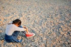 Λυπημένος μια συνεδρίαση κοριτσιών στο ξηρό έδαφος Στοκ Φωτογραφίες