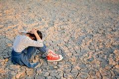 Λυπημένος μια συνεδρίαση κοριτσιών στο ξηρό έδαφος Στοκ Φωτογραφία