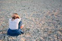 Λυπημένος μια συνεδρίαση κοριτσιών στο ξηρό έδαφος Στοκ φωτογραφίες με δικαίωμα ελεύθερης χρήσης