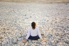 Λυπημένος μια συνεδρίαση κοριτσιών στο ξηρό έδαφος Στοκ φωτογραφία με δικαίωμα ελεύθερης χρήσης