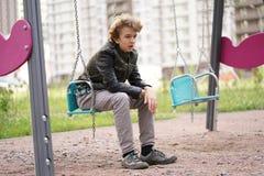 Λυπημένος μόνος έφηβος υπαίθριος στην παιδική χαρά οι δυσκολίες της εφηβείας στην έννοια επικοινωνίας στοκ εικόνα
