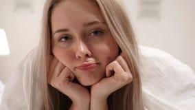 Λυπημένος νέος στενός επάνω προσώπου γυναικών στο κρεβάτι απόθεμα βίντεο