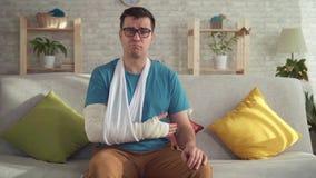 Λυπημένος νεαρός άνδρας πορτρέτου στα γυαλιά με το σπασμένο βραχίονα απόθεμα βίντεο
