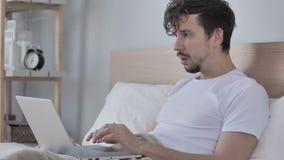 Λυπημένος νεαρός άνδρας που αντιμετωπίζει την απώλεια χρησιμοποιώντας το lap-top στο κρεβάτι απόθεμα βίντεο