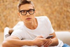 Λυπημένος νεαρός άνδρας που κρατά το τηλέφωνό του Στοκ Φωτογραφίες