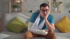 Λυπημένος νεαρός άνδρας στα γυαλιά με το σπασμένο βραχίονα απόθεμα βίντεο