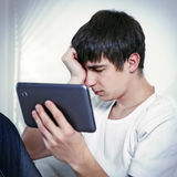 Λυπημένος νεαρός άνδρας με την ταμπλέτα Στοκ Φωτογραφίες