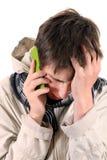 Λυπημένος νεαρός άνδρας με το κινητό τηλέφωνο Στοκ Εικόνες