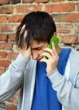 Λυπημένος νεαρός άνδρας με το κινητό τηλέφωνο Στοκ εικόνες με δικαίωμα ελεύθερης χρήσης