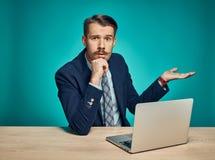 Λυπημένος νεαρός άνδρας που εργάζεται στο lap-top στο γραφείο Στοκ Φωτογραφίες