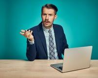 Λυπημένος νεαρός άνδρας που εργάζεται στο lap-top στο γραφείο Στοκ Εικόνες