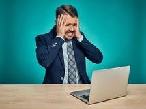 Λυπημένος νεαρός άνδρας που εργάζεται στο lap-top στο γραφείο Στοκ Φωτογραφία