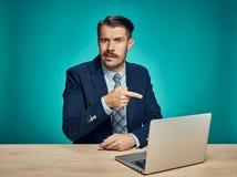 Λυπημένος νεαρός άνδρας που εργάζεται στο lap-top στο γραφείο Στοκ φωτογραφία με δικαίωμα ελεύθερης χρήσης