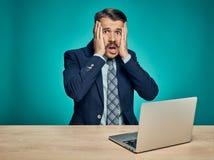 Λυπημένος νεαρός άνδρας που εργάζεται στο lap-top στο γραφείο Στοκ εικόνα με δικαίωμα ελεύθερης χρήσης