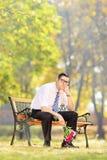 Λυπημένος νεαρός άνδρας που κρατά μια ανθοδέσμη των λουλουδιών και που κάθεται στον πάγκο Στοκ Εικόνες