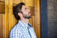 Λυπημένος νεαρός άνδρας που κλίνει στην πόρτα Στοκ φωτογραφία με δικαίωμα ελεύθερης χρήσης