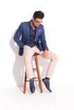 Λυπημένος νεαρός άνδρας στη συνεδρίαση και το κοίταγμα κοστουμιών κάτω Στοκ Εικόνες