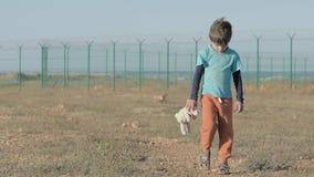 Λυπημένος ορφανός αγοριών που περπατά κατά μήκος του εγκαταλειμμένου δρόμου με το κεφάλι κάτω στα χέρια του κρατήματος ενός κουνε φιλμ μικρού μήκους