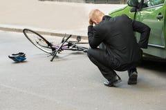 Λυπημένος οδηγός μετά από τη σύγκρουση με το ποδήλατο στοκ εικόνες