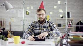 Λυπημένος προσηλωμένος ελκυστικός επιχειρηματίας που γιορτάζει μόνα γενέθλια στο γραφείο, φυσά ένα κερί σε ένα μικρό κέικ φιλμ μικρού μήκους