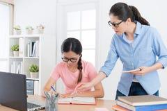 Λυπημένος σπουδαστής κοριτσιών που γράφει μελετώντας το βιβλίο δοκιμής διαγωνισμών Στοκ εικόνα με δικαίωμα ελεύθερης χρήσης