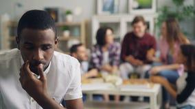 Λυπημένος τύπος αφροαμερικάνων που κάθεται μόνο ενώ οι εύθυμοι φίλοι  απόθεμα βίντεο