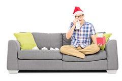 Λυπημένο άτομο με το καπέλο Santa που σκουπίζει τα μάτια του από να φωνάξει στοκ εικόνα