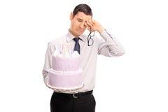 Λυπημένο άτομο που κρατά ένα κέικ και να φωνάξει γενεθλίων Στοκ Εικόνες