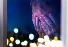 Λυπημένο άτομο που φωνάζει αργά τη νύχτα από ένα παράθυρο στοκ εικόνες