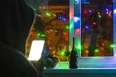 λυπημένο άτομο σε μια κουκούλα με ένα smartphone θολωμένο bokeh, στο υπόβαθρο του παραθύρου που διακοσμείται με τις γιρλάντες με  στοκ φωτογραφία με δικαίωμα ελεύθερης χρήσης