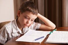 Λυπημένο αγόρι που κάνει την εργασία Στοκ Εικόνες