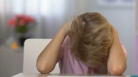 Λυπημένο αγόρι που κουράζεται της περίπλοκης εργασίας, που πέφτει κοιμισμένης στον πίνακα, εξαγωγή απόθεμα βίντεο