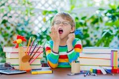 Λυπημένο αγόρι σχολικών παιδιών με τα γυαλιά και την ουσία σπουδαστών Στοκ Εικόνες