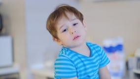 Λυπημένο αγόρι τρία προσώπου χρονών, που κάθεται στην κουζίνα στο σπίτι και που μιλά στη κάμερα απόθεμα βίντεο