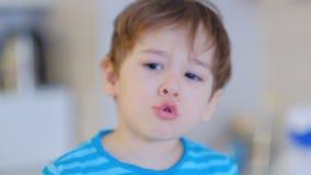 Λυπημένο αγόρι τρία προσώπου χρονών, που κάθεται στην κουζίνα στο σπίτι και που μιλά στη κάμερα φιλμ μικρού μήκους