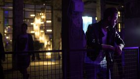 Λυπημένο αρσενικό που στέκεται κοντά στη αίθουσα συναυλιών και που σκέφτεται για την πρώην-φίλη, προβλήματα απόθεμα βίντεο