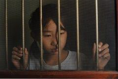 Λυπημένο ασιατικό παιδί που στέκεται πίσω από το παράθυρο οθόνης καλωδίων στο σκοτεινό μ Στοκ Εικόνες