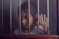Λυπημένο ασιατικό παιδί που στέκεται πίσω από το παράθυρο οθόνης καλωδίων στο σκοτεινό μ Στοκ Φωτογραφία